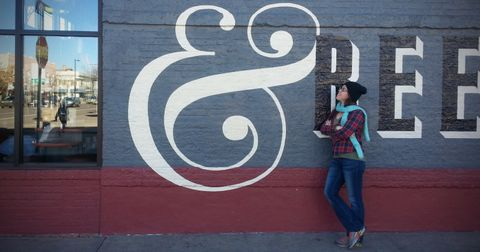 Sondra looks at large ampersand symbol painted on building exterior