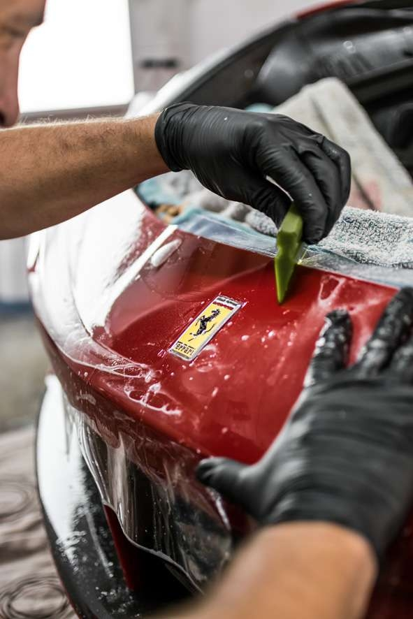 Paint protection film (PPF) being applied to red Ferrari 458 GTB badge and front bumper