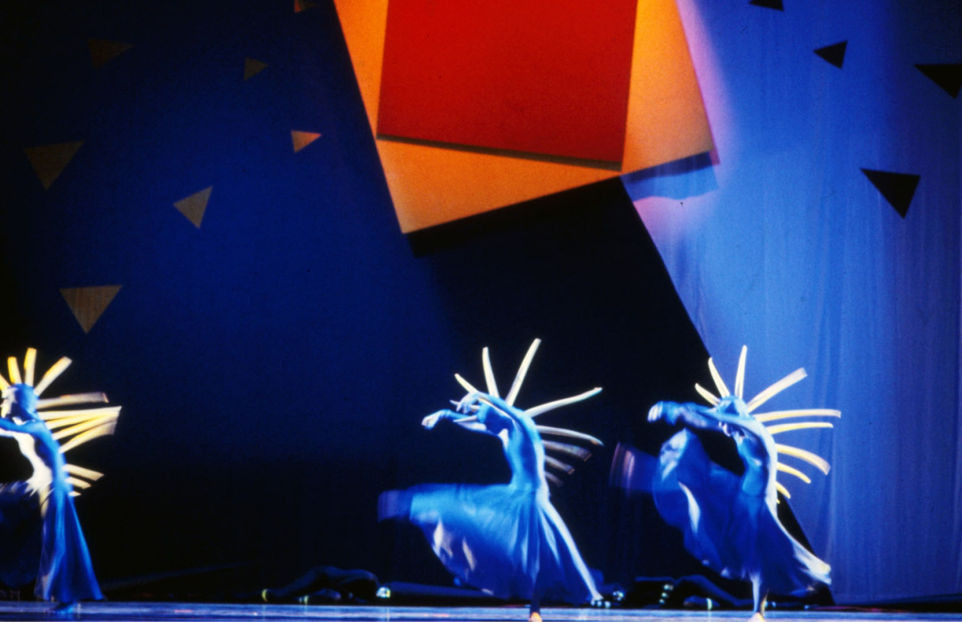 Three blue-garbed dancers with yellow spine spikes gyrate against brightly coloured geometric background.