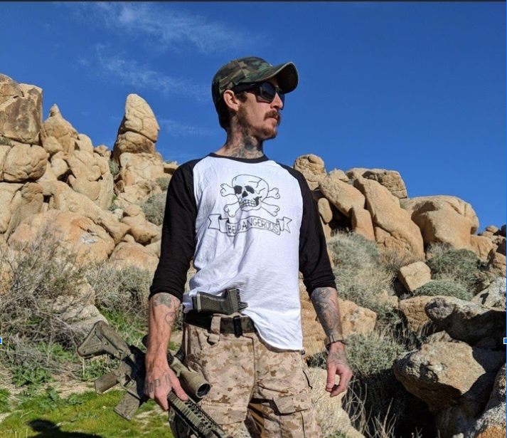 A man poses in the desert with a camoflauge-painted rifle in one hand and a gun tucked into his waistband. He's wearing a shirt with a totenkopf, a stylized a skull and crossbones nazi soldiers would wear.