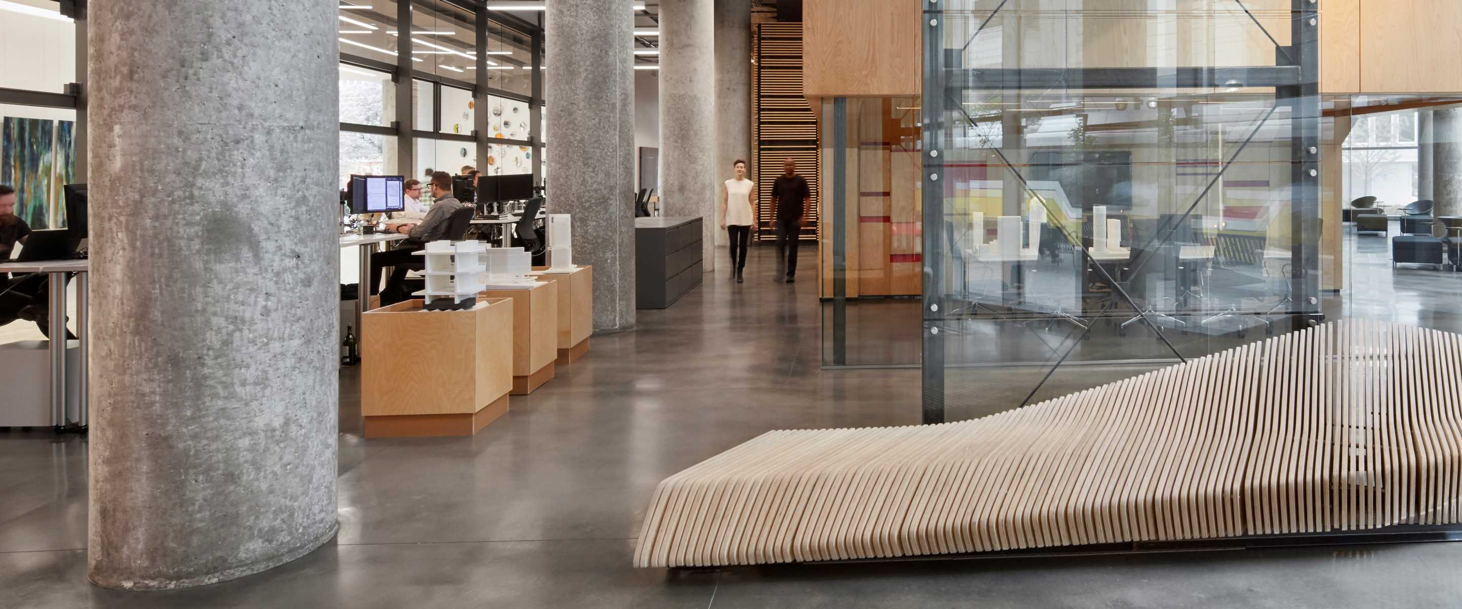 Two workers walking down corridor in stylish concrete and wood office