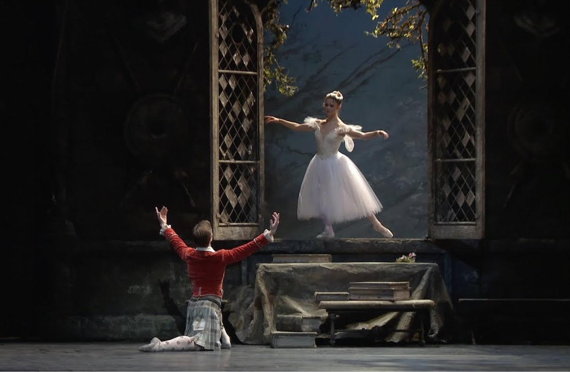 Dancer in kilt and red jacket knees before ballerina in white dress poised in open window.
