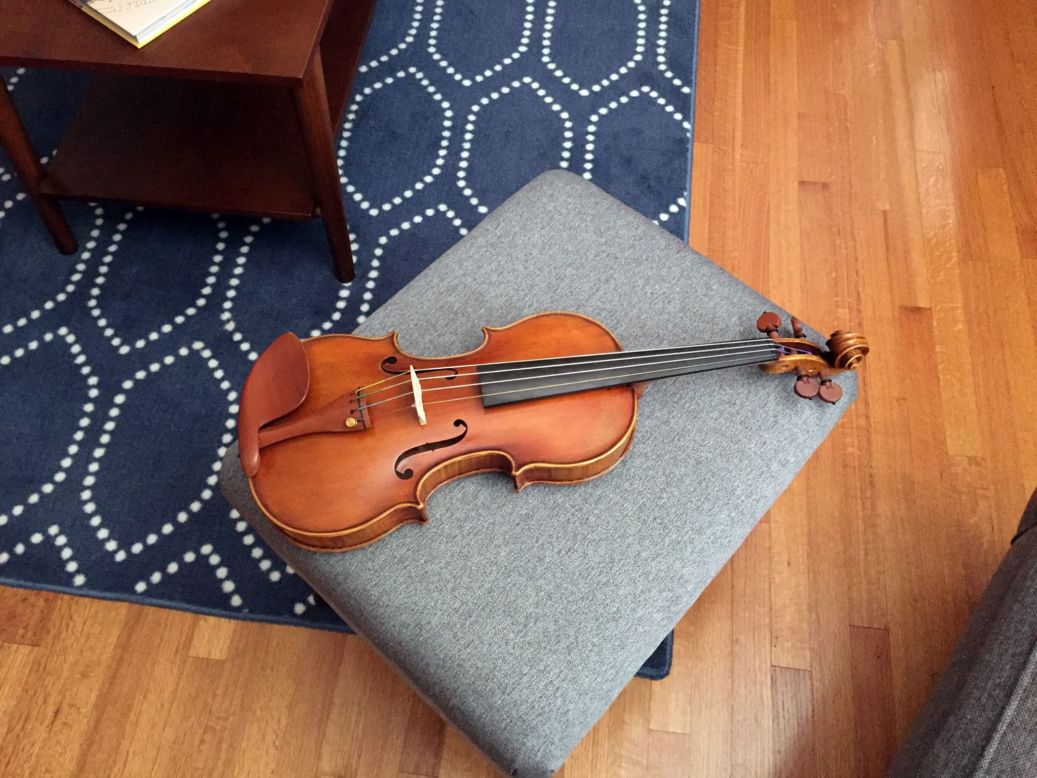 Picture of a brown violin sitting on a gray ottoman