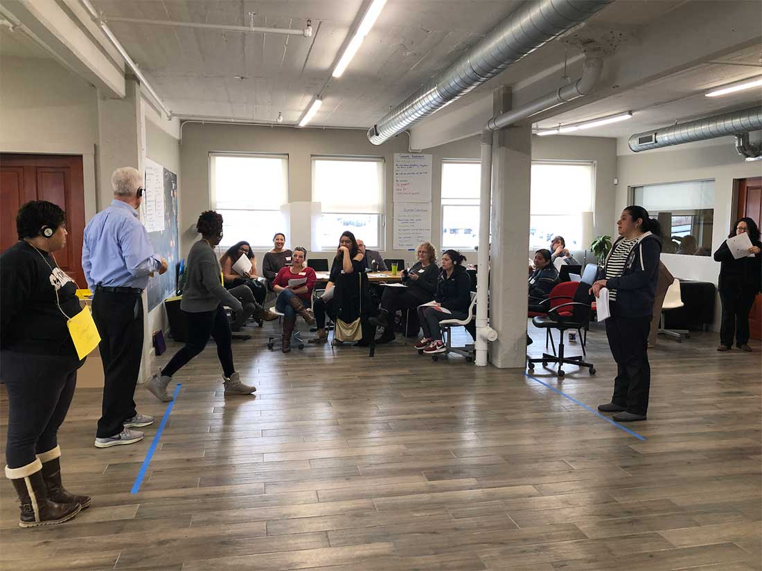 Photograph showing people in a large room engaging in the Convince Me! workshop. The room has two lines of blue tape set up on the floor, and a group of participants stands behind one line facing another participant who stands at the second line and is talking to them.