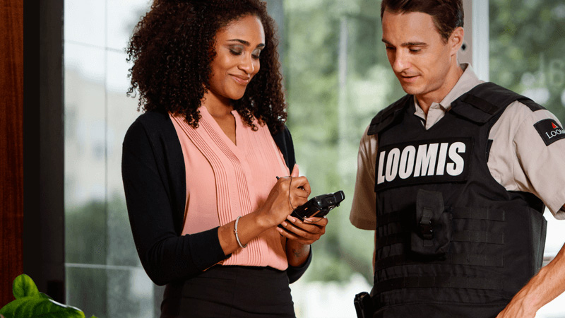 A photo of a businesswoman holding a mobile device and a man wearing a Loomis armored protection vest