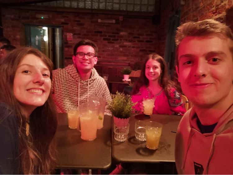 Myself, Naomi and my friends James and Siobhan sat around a table holding a variety of different coloured cocktails. This was taken after completing an escape room for my birthday. Asa result, we're wearing stickers that say, We excaped!