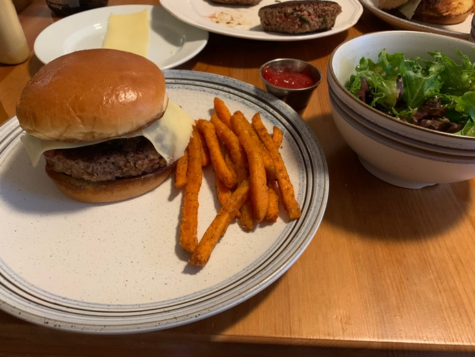 Finished veggie burgers with sweet potato fries and salad