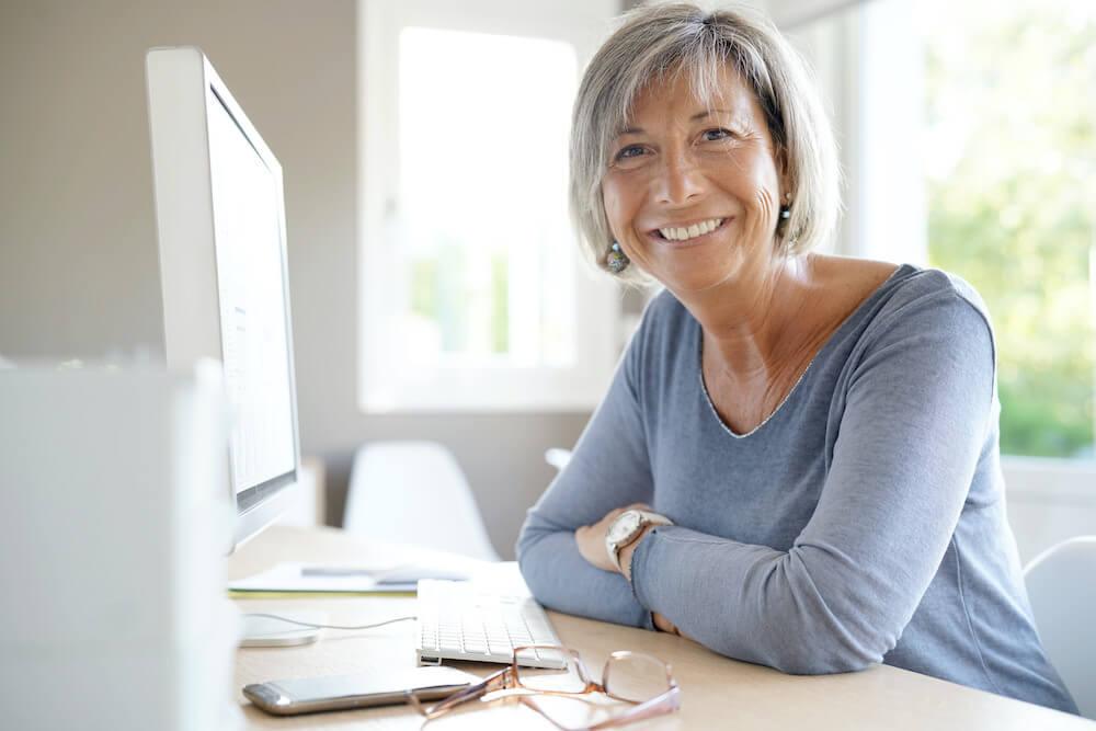 lächelnde Rentnerin am Arbeitsplatz