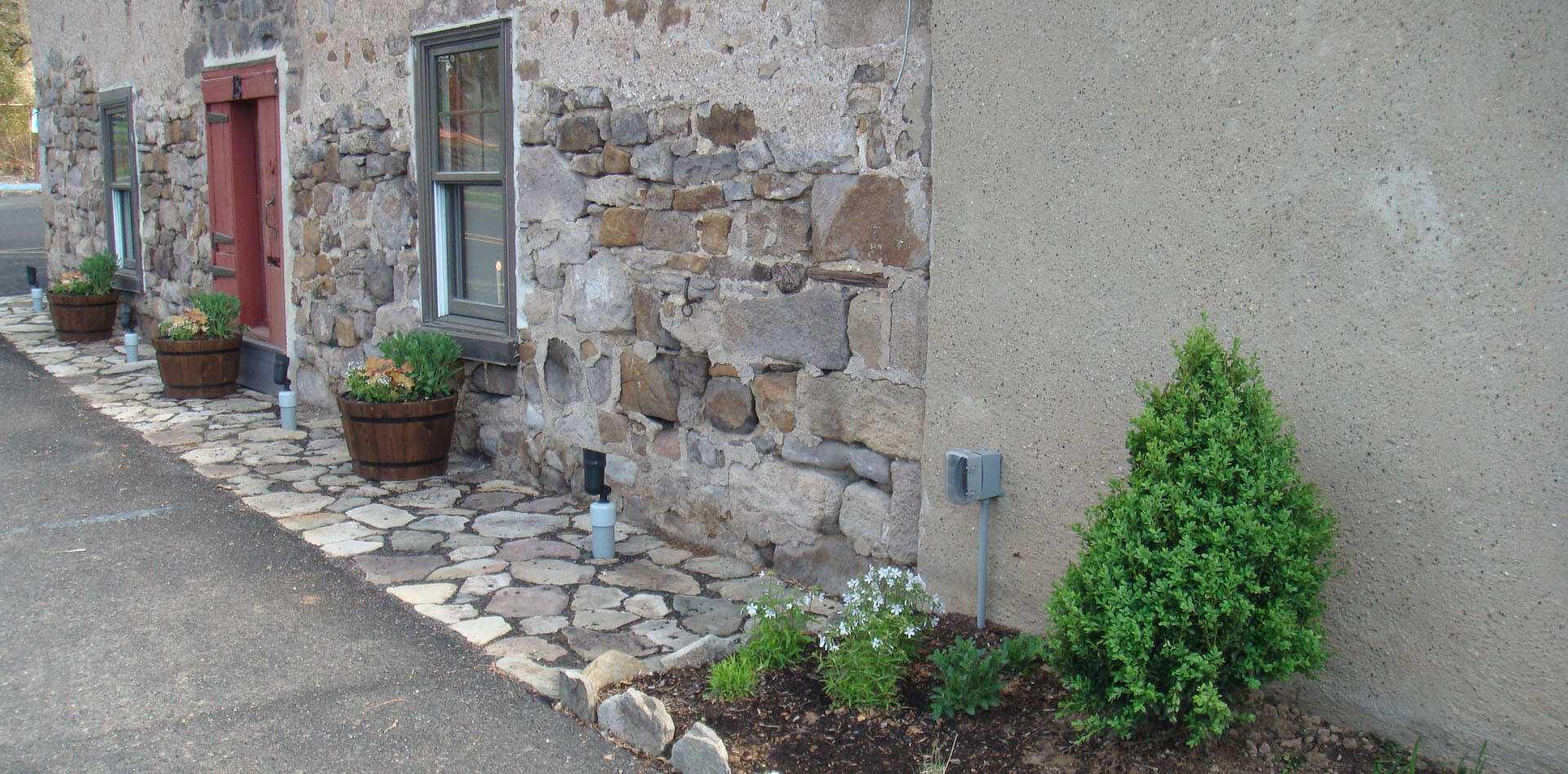 flower beds alongside edge of stone wall