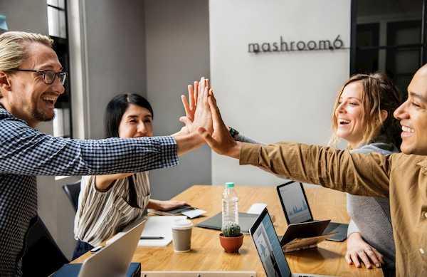 Cuatro personas chocando las manos en una reunión