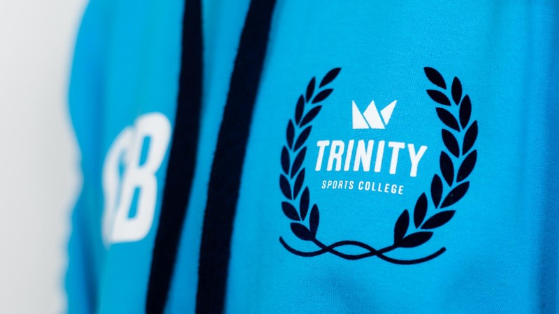 A close-up of a blue ski hoodie with a sports college logo printed on the front left chest