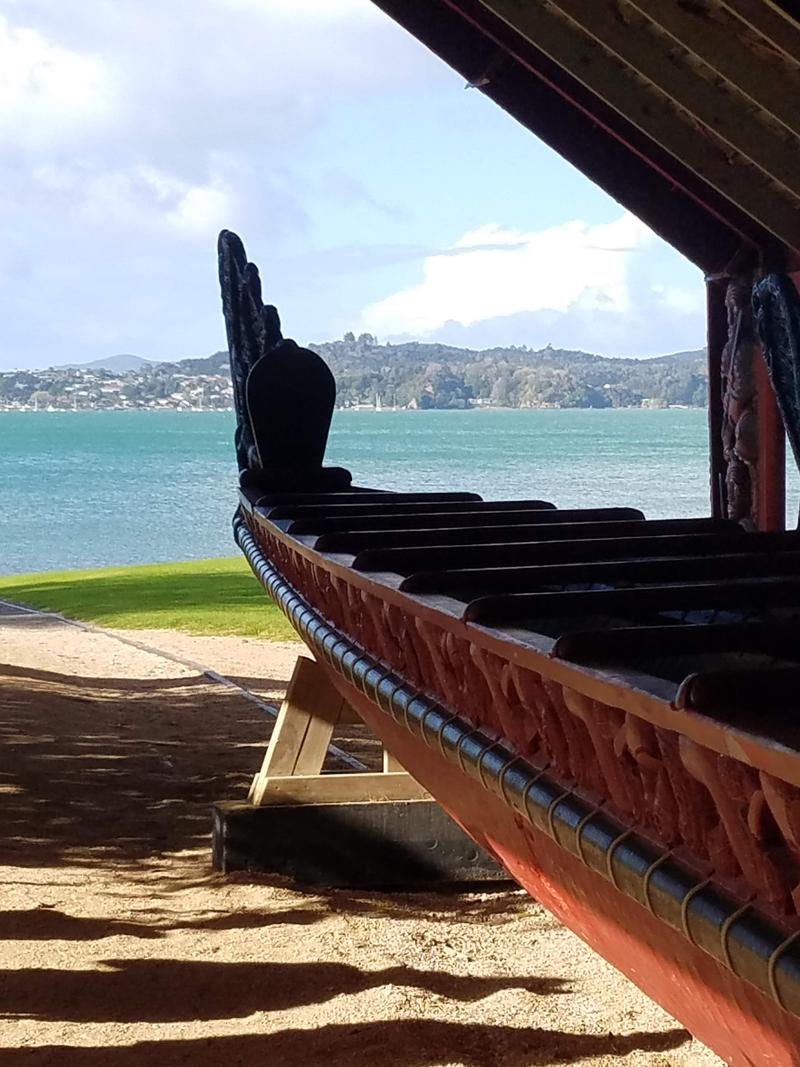 Maori war canoe on tracks to the bay