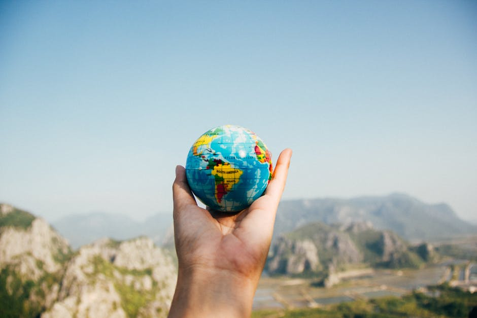 Person holding miniature globe in hand