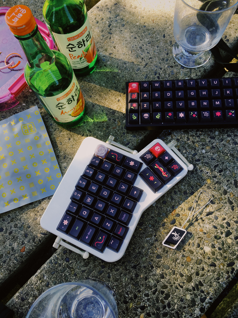 Keyboards and soju on a park table.