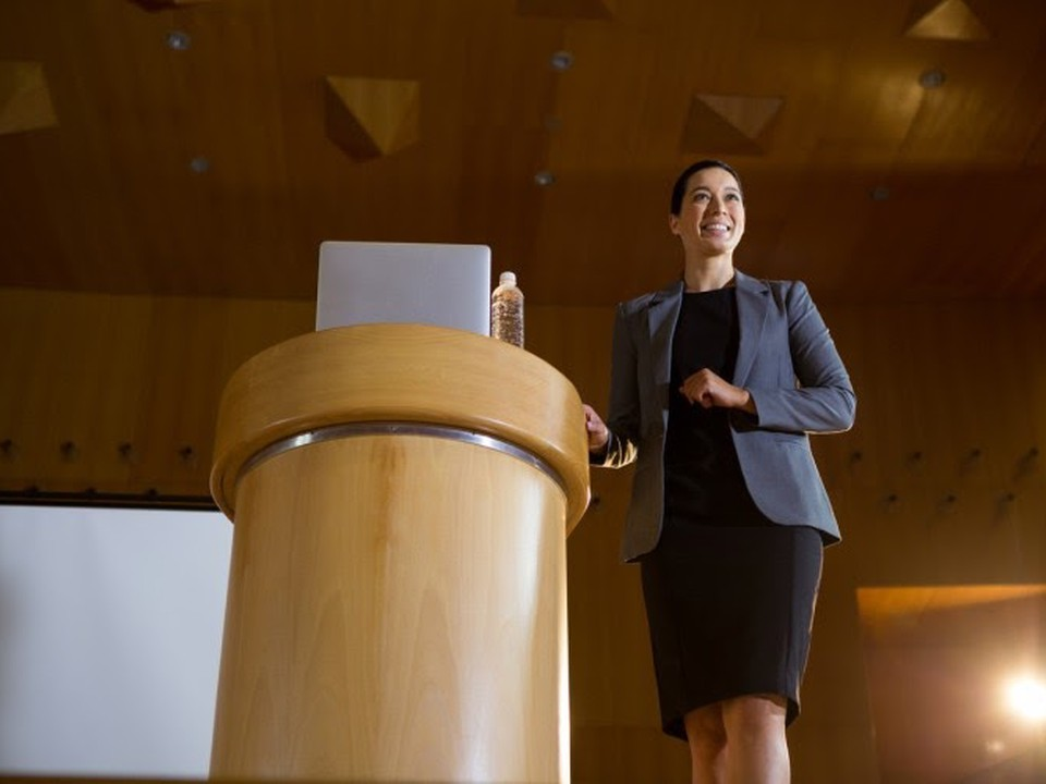 A smiling school administrator in business attire stands next to a wooden podium in a lecture hall.