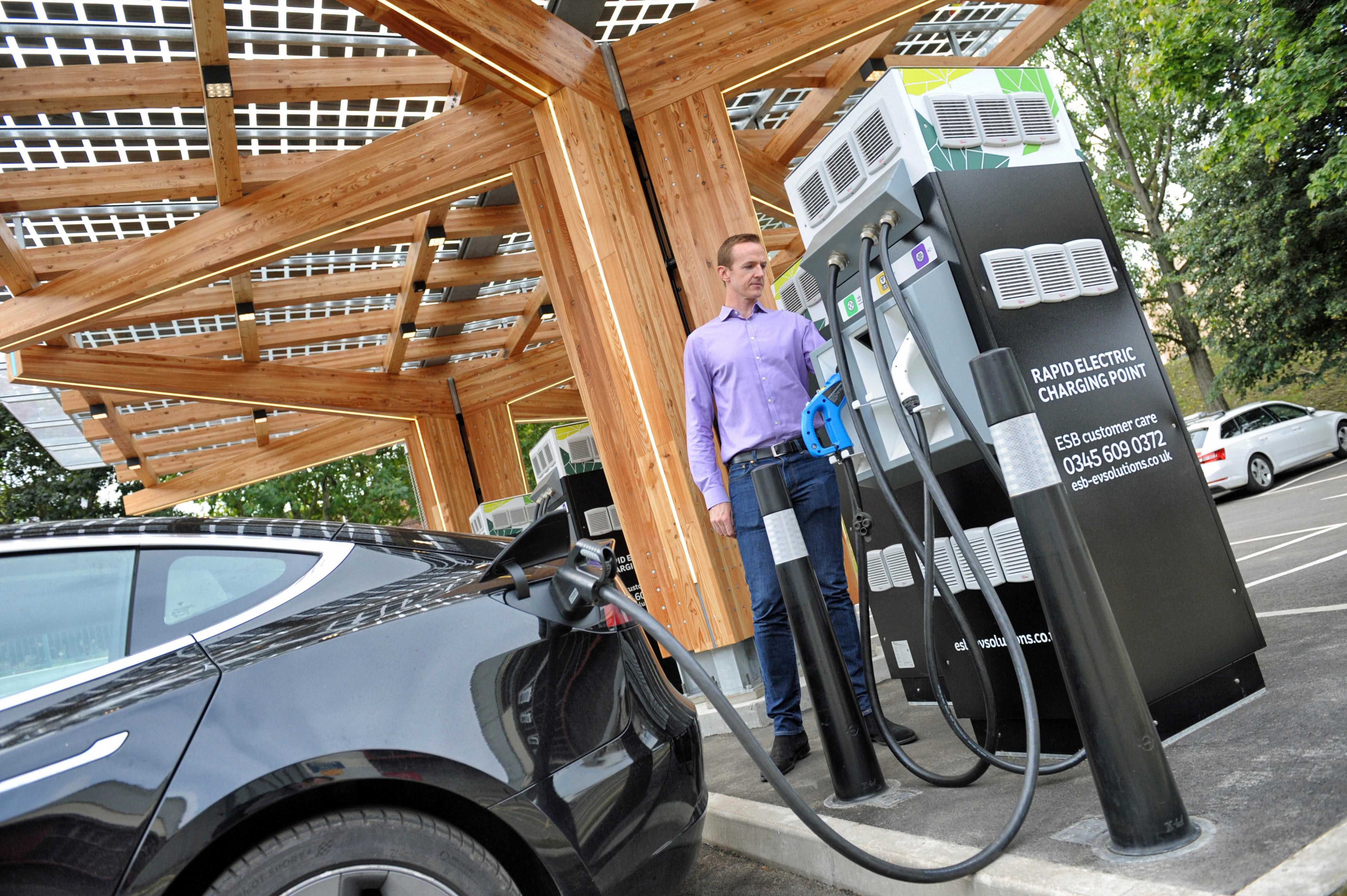 A man demonstrates K:Port in use by charging a Tesla electric car under the canopy