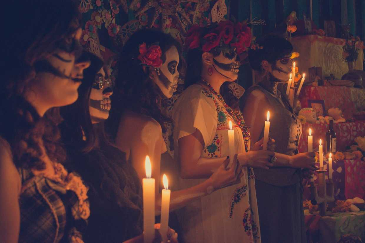 Image of people gateher with lights on Dia de los Muertos