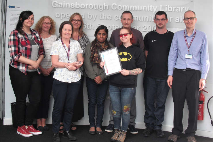 Nine members of Gainsborough Library staff displaying their award certificate