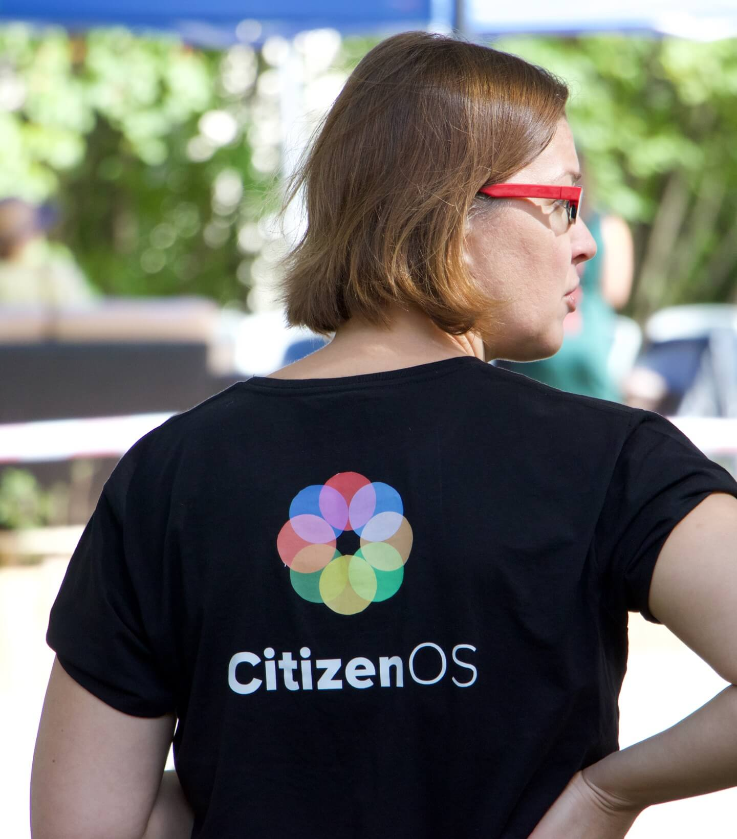 A female member of Citizen OS staff attending an event to answer questions about the platform.