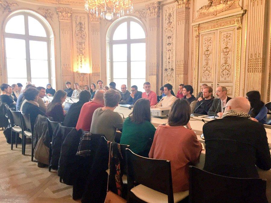 Plan d'ensemble d'une quarantaine de personnes autour d'une table, dans une salle de réunion agrémentée de dorures.