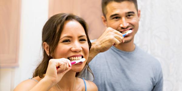 Two people brushing their teeth together in a bathroom