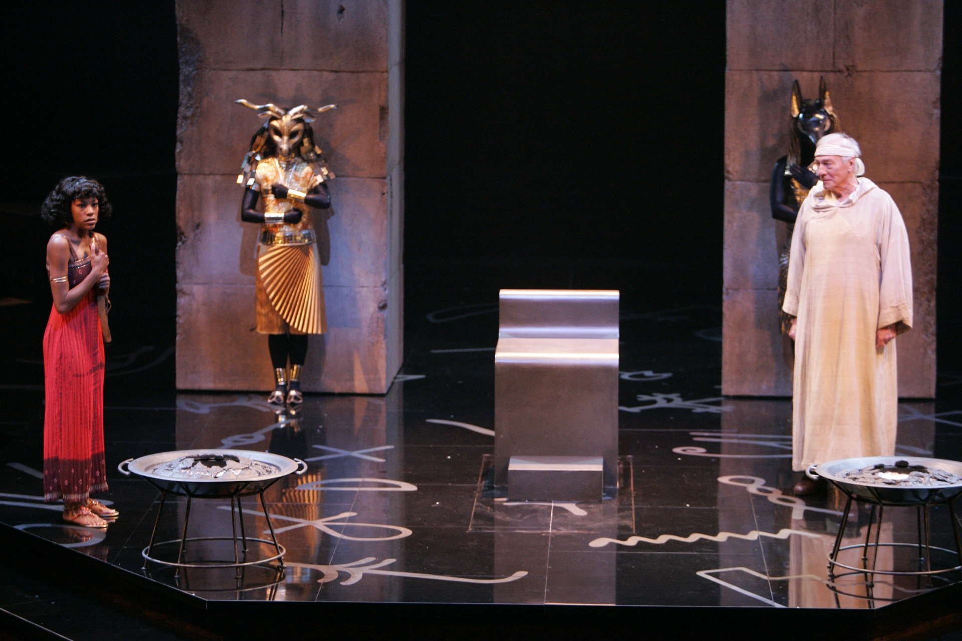 Girl in red dress speaks to old man in white gown on shiny black floor; guards in Egyptian masks behind.