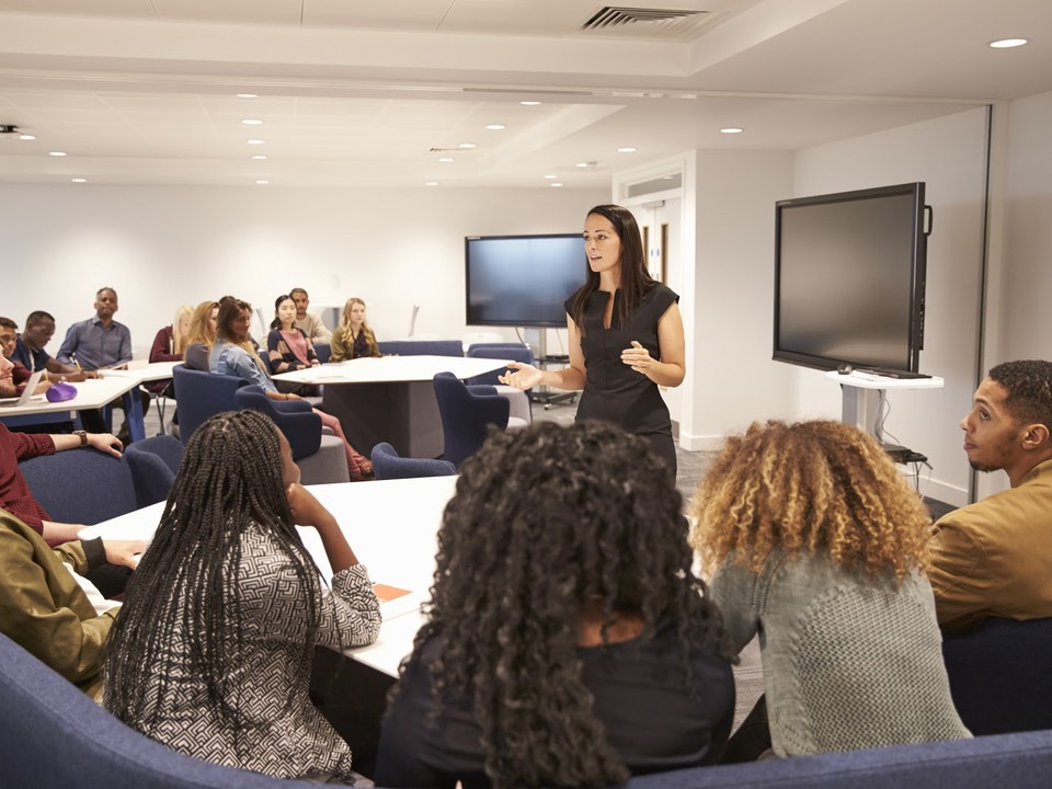 Educator lectures to students in a classroom.