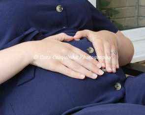 Image of expecting mother and her baby bump. Making a heart shape on top of her bump using her hands.