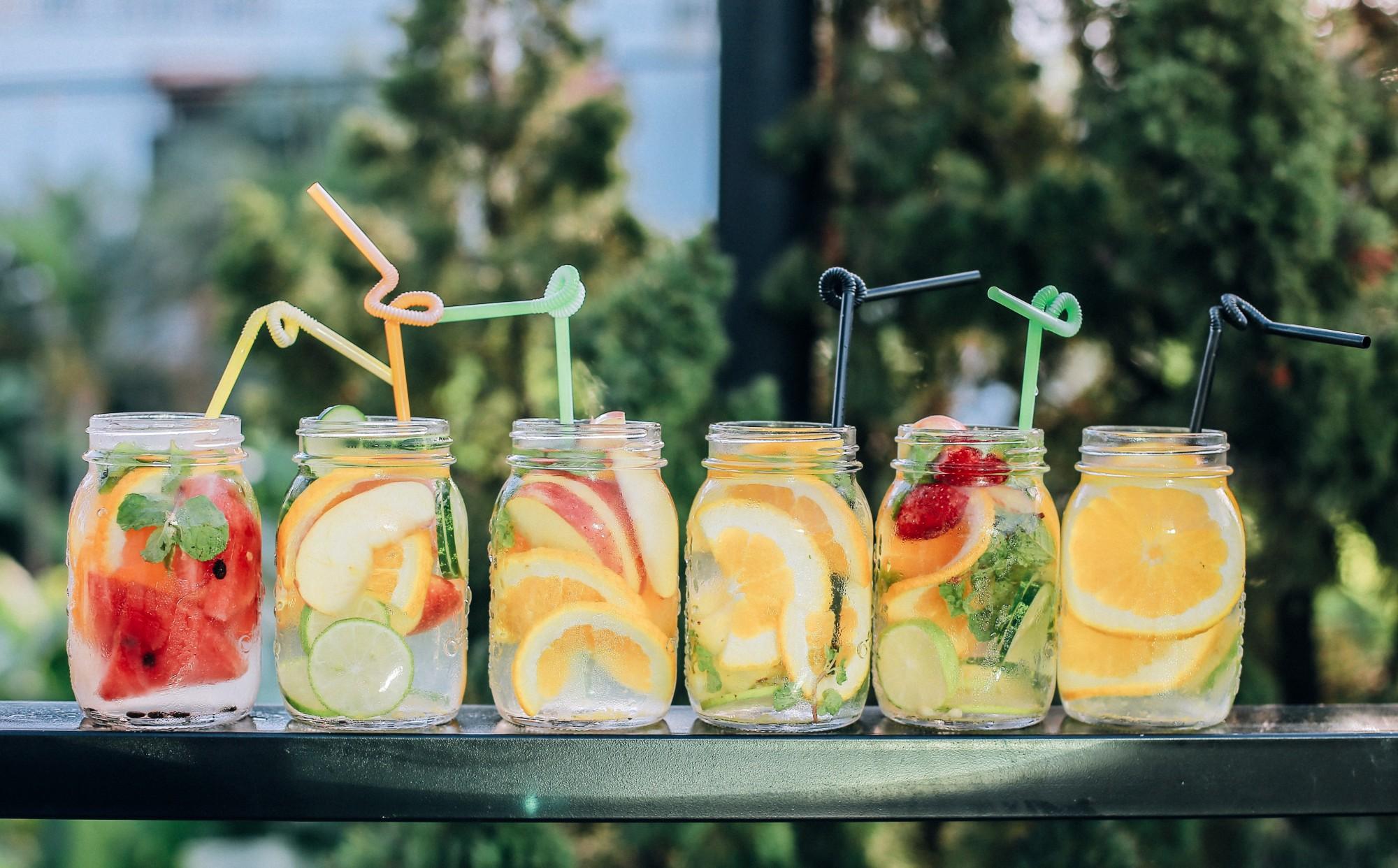 Imagem de drinks tropicais com frutas dentro de copos de vidro com canudos de cores diferentes. Foto por Kaizen Nguyễn no Unsplash