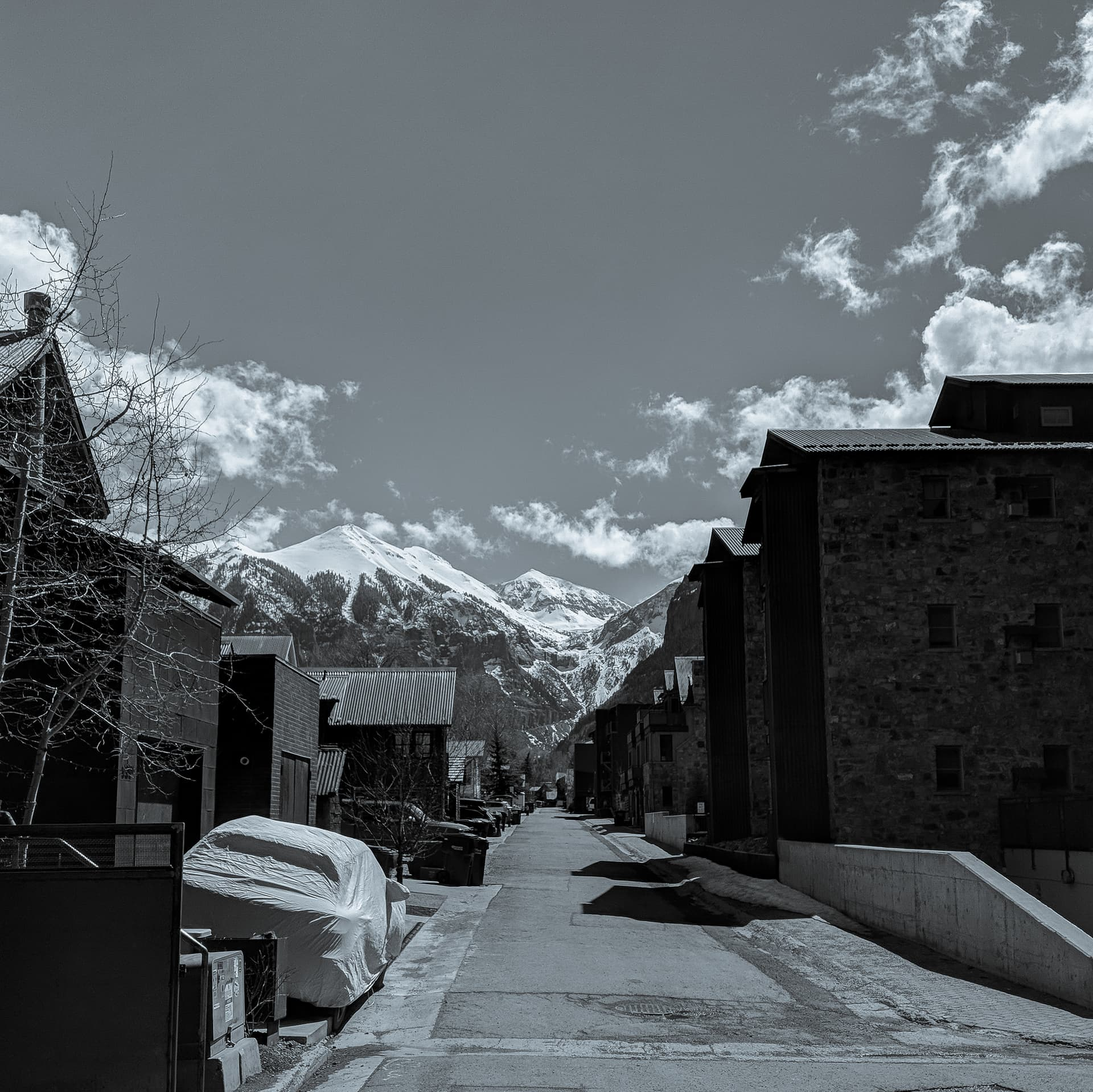 Looking down the road in a mountain town. Beyond the rooftops, three distinctly triangular snow-capped peaks can be seen.