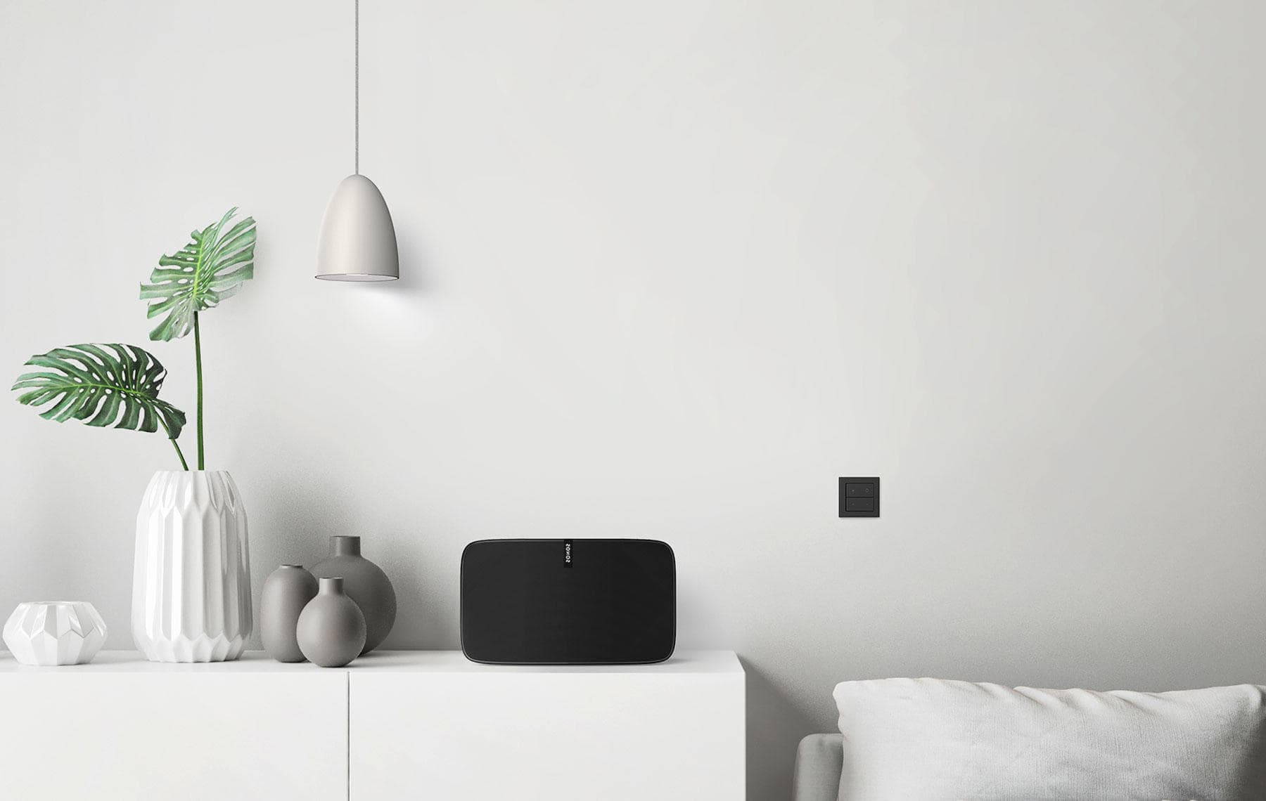 Nuimo Click Schwarz fixed on a Weiß wall in a sophisticated living room next to a Sonos speaker and stylish furniture