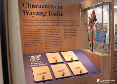 A roving exhibition wall titled: Characters in Wayang Kulit. Like the Chinese Opera section, it also features 4 wooden panels below it about different character types. A wooden puppet on stilts is hung on the right of the wall