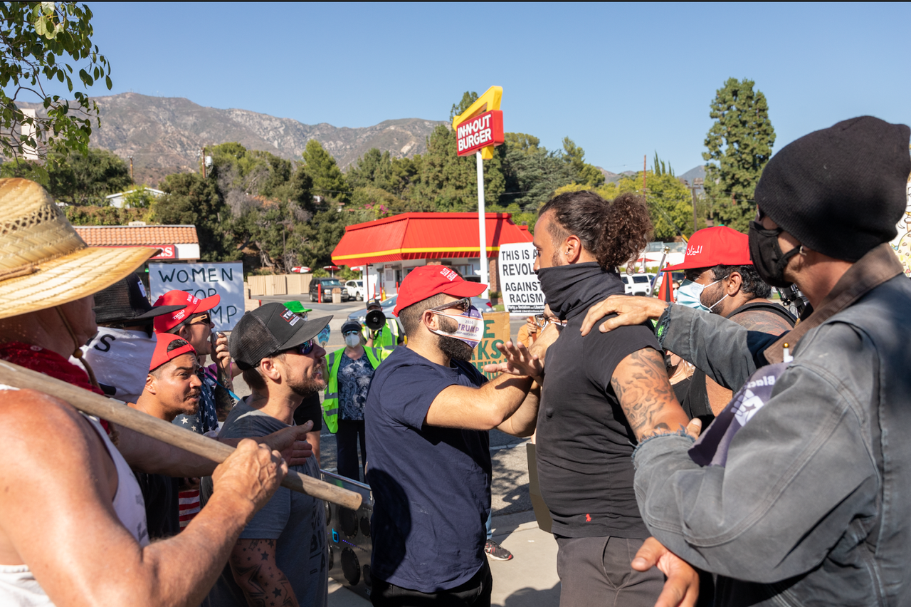 Right-wingers push a protester in front as his arms are extended, blocking those behind him.
