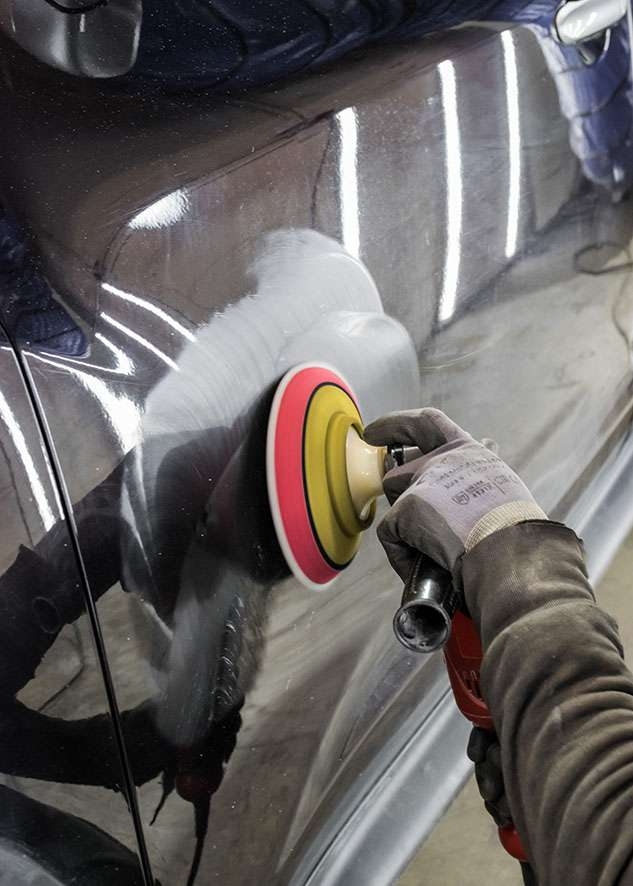 Black Nissan Juke car paintwork being machined polished to remove scratches