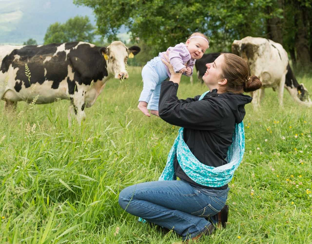 A young mother lovingly holding her baby in a pasture as cows graze in the background.
