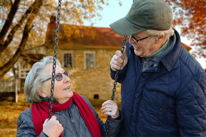 Two aged adults in a park with one swinging on a cold fall day.