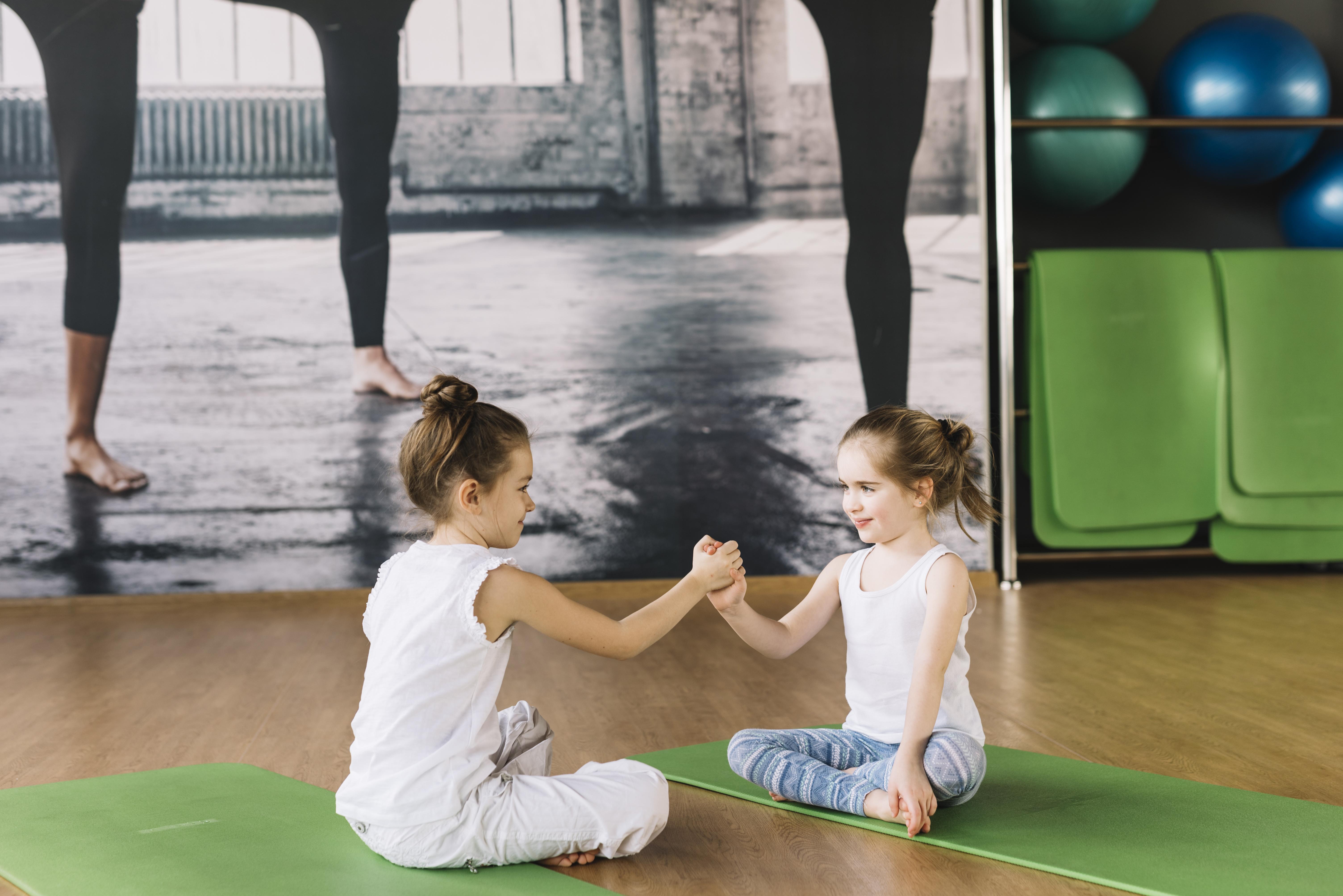 Two children sitting on yoga mats.