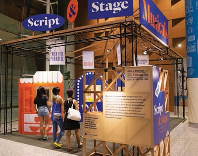 A photo of the lobby exhibition: Script and Stage - Musicals. Three people are entering the exhibition. It is shaped like an open box, supported by black metal railings. Small banners hang from its ceiling, and small wall displays are inside the exhibition.