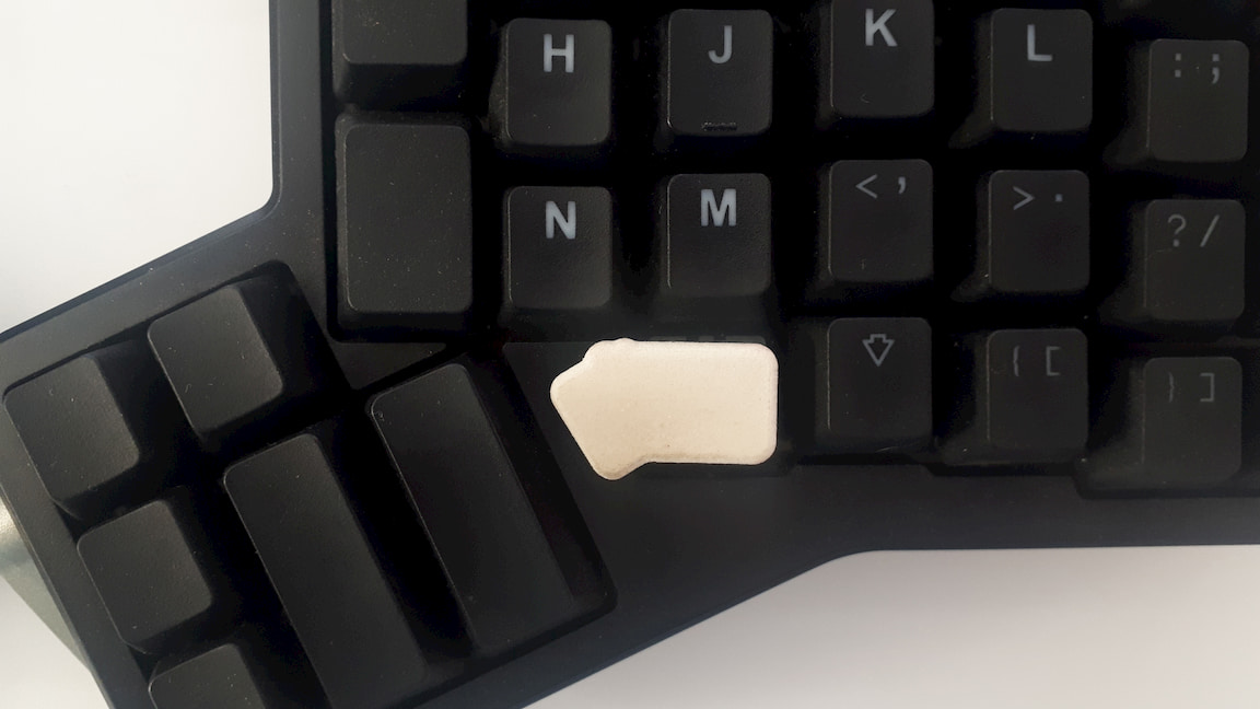A custom, 3D printed keycap. Standing out on the keyboard, just before the thumb clusters.