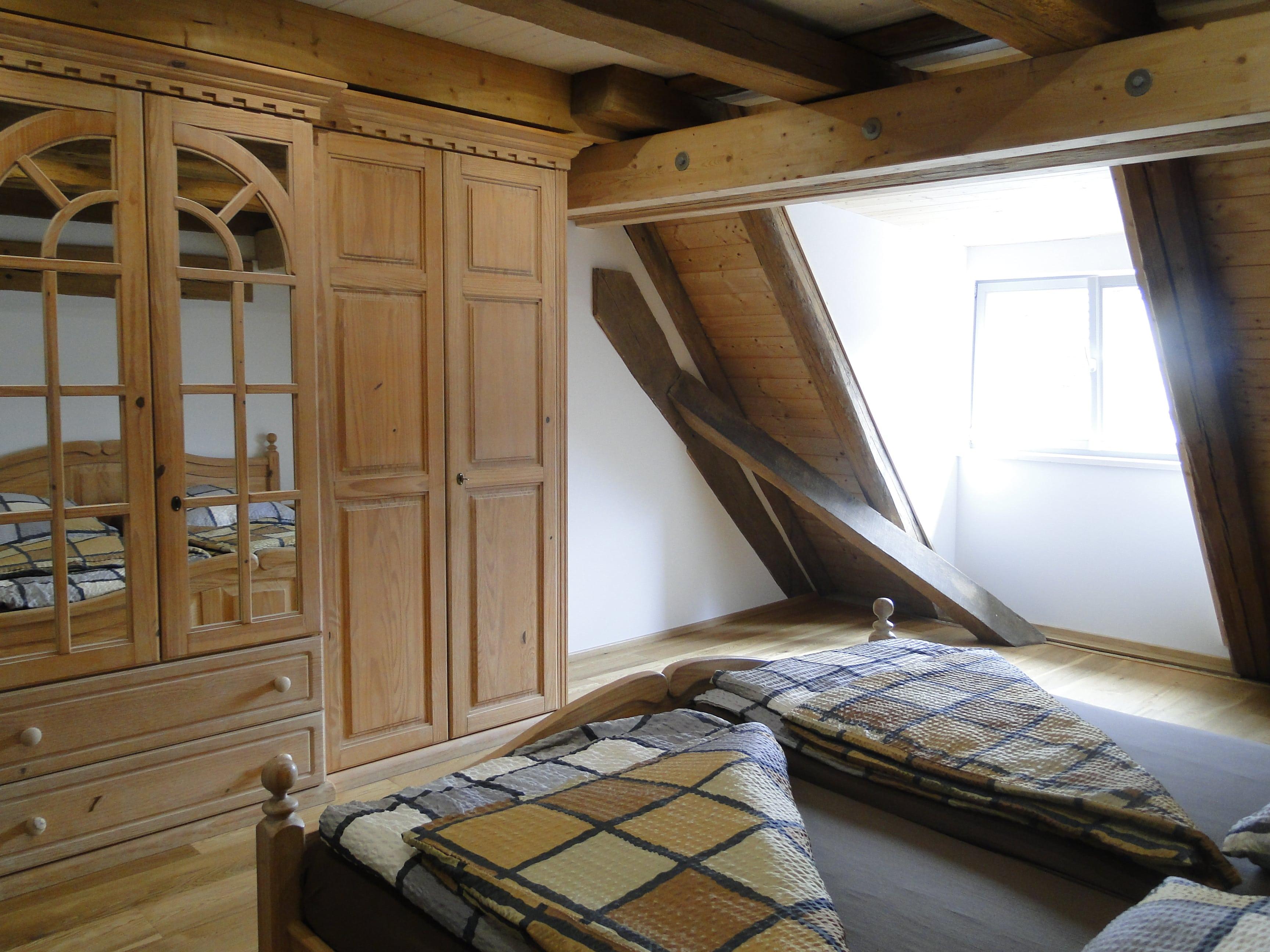 Schlafzimmer mit Doppelbett und Holzschrank