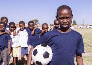 Children posing with soccer ball