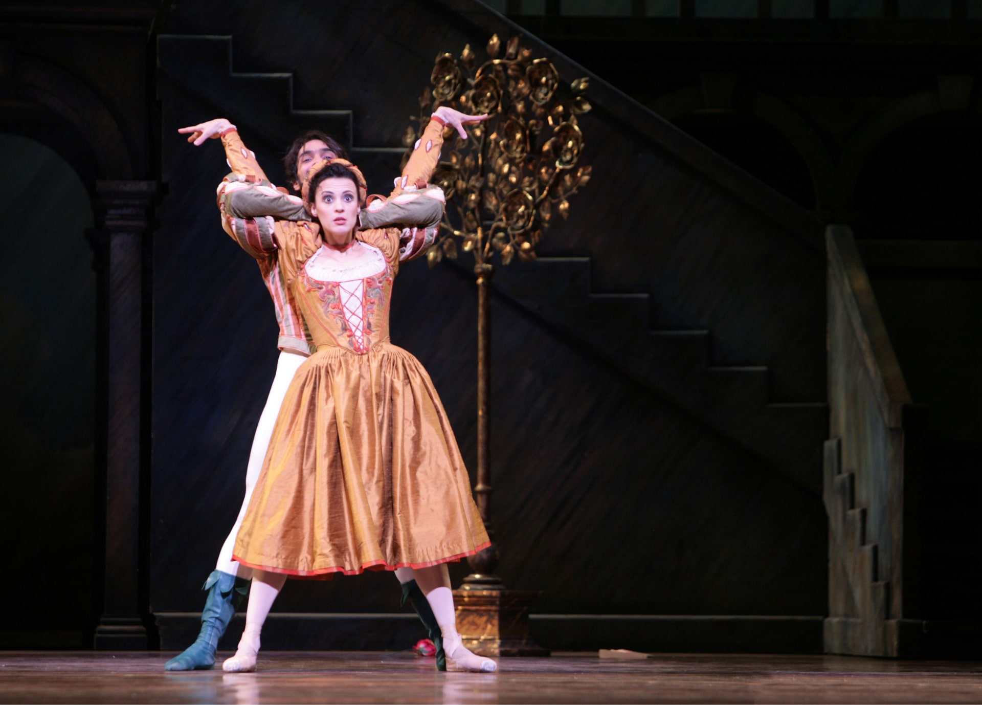 Ballerina in orange dress is restrained by dancer behind her near gold standing tree and painted staircase.