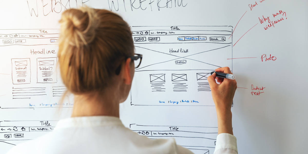 UX design student drawing wireframes on a whiteboard.