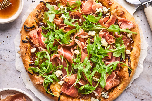 Fig Prosciutto Gorgonzola and Arugula Pizza With Hot Honey