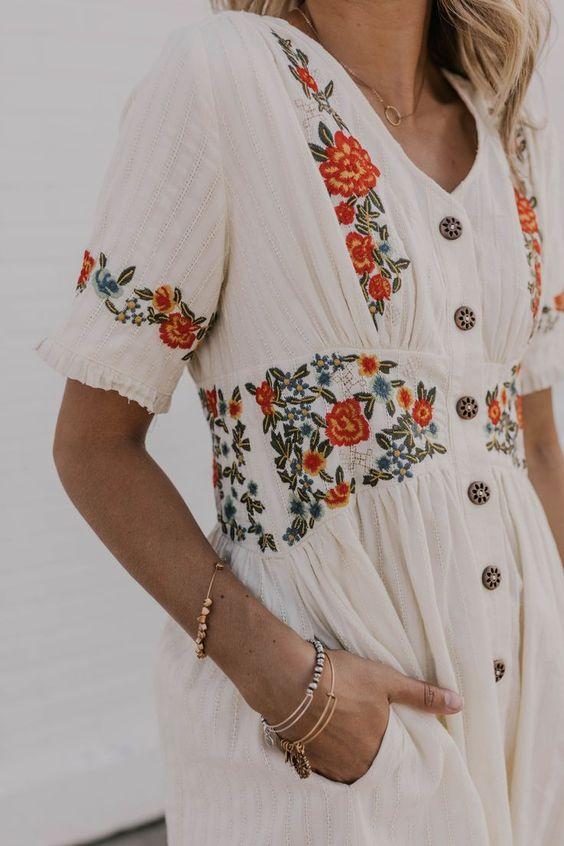 Robe blanche brodée de fleurs rouges et oranges