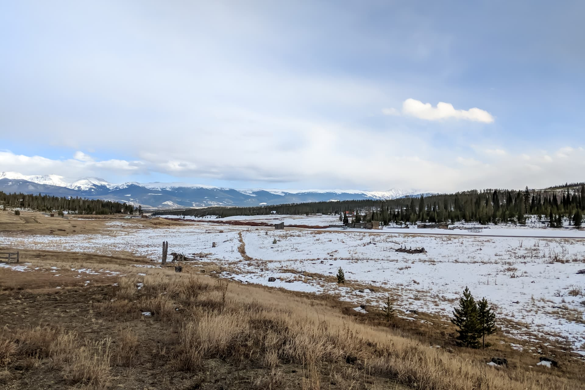 Looking out across a snowy high country ranch. In the distance, the Rocky Mountains.