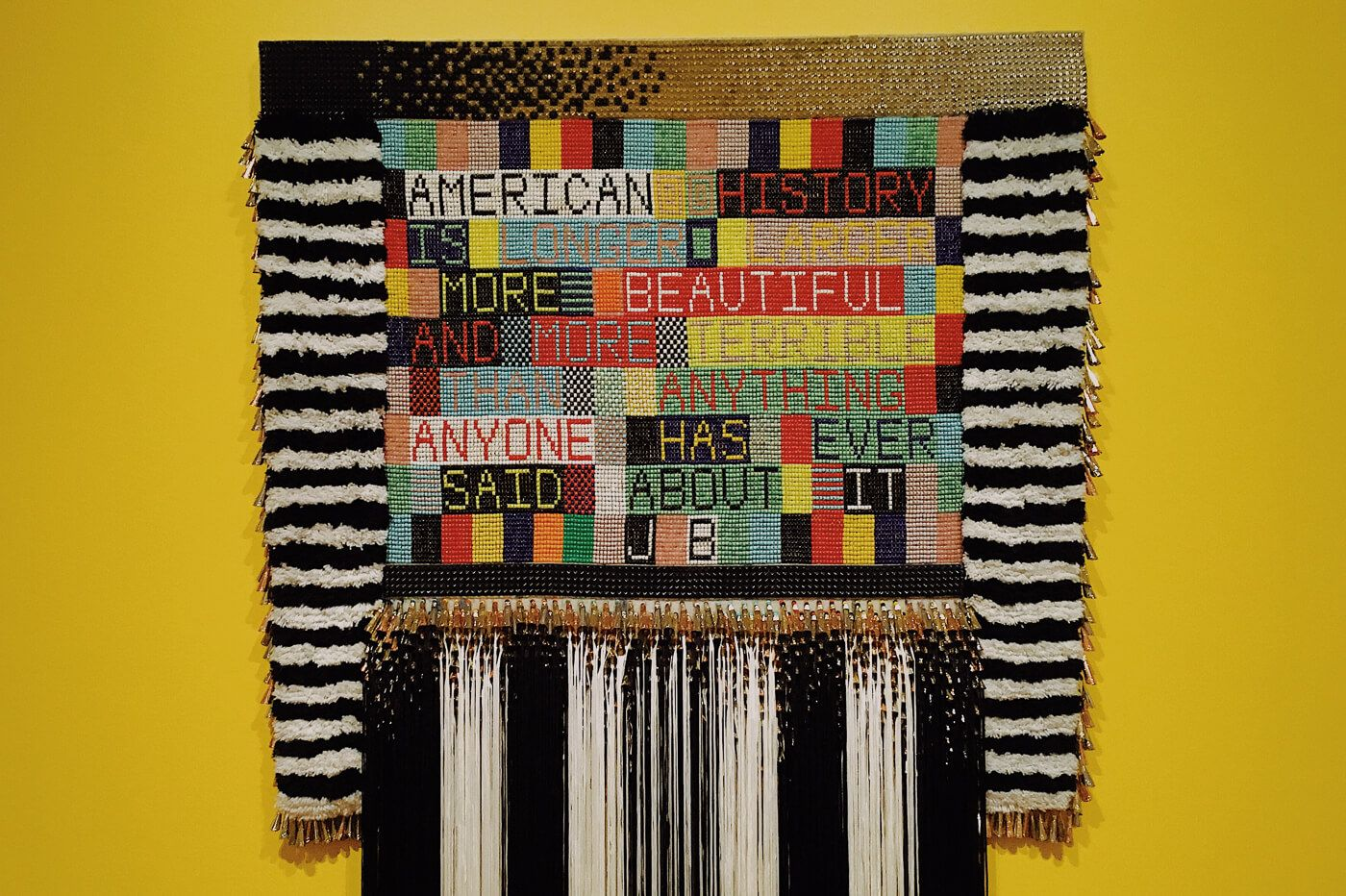Text woven into a colourful textile
