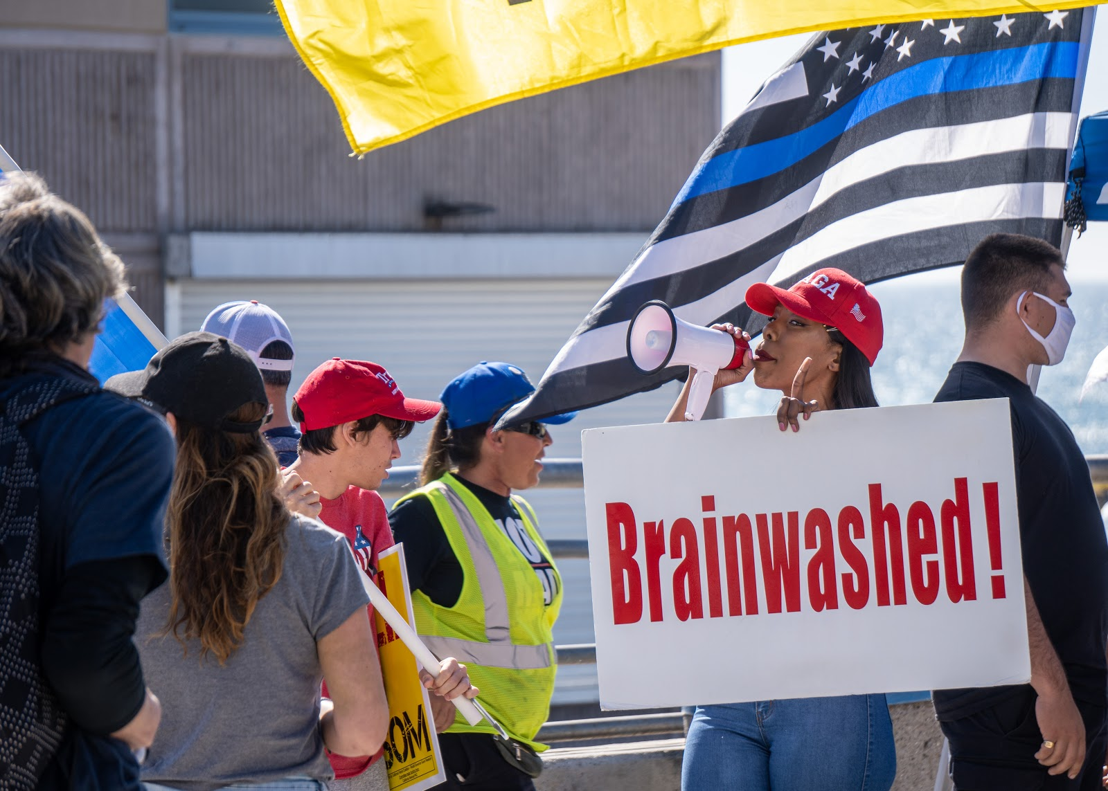 there is a dark skinned maskless woman wearing a maga hat and holding up a white sign in one hand with red text that reads 'Brainwashed!' and the other hand holds a small megaphone at the end. there is a thin blue line flag held by a man wearing a white mask there is the edge of a yellow flag above the thin blue line flag to the left of those two people are several maskless people, some looking towards the person holding th megaphone, others facing away