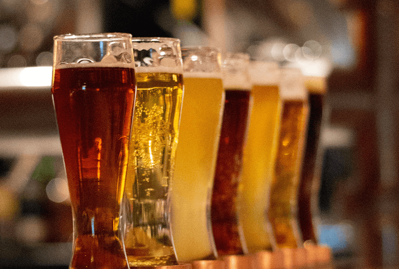 AB inBEV Beers Poured in Several Glasses Lined Up in a Row