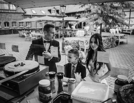 Brautpaar mit einem Kind schaut voller Vorfreude bei der Zubereitung eines Crêpe mit Kinderriegel zu
